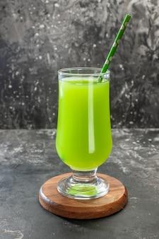 Vista frontal de jugo de manzana verde dentro de un vaso con pajita en color claro, bebida de cóctel, fruta