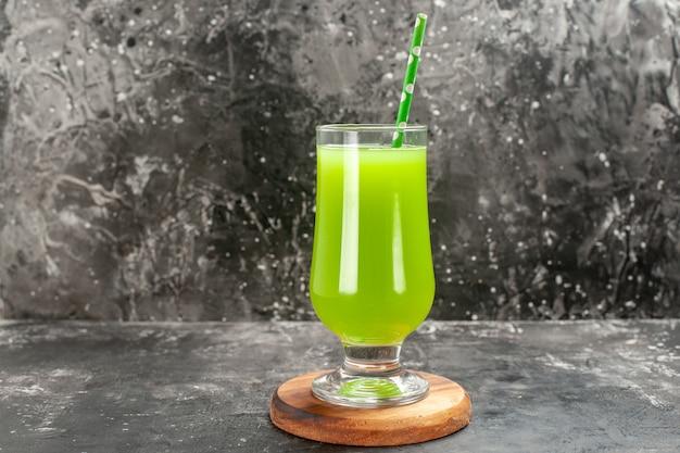Vista frontal de jugo de manzana verde dentro del vaso con pajita en color gris claro, bebida fotográfica, barra de cócteles, fruta
