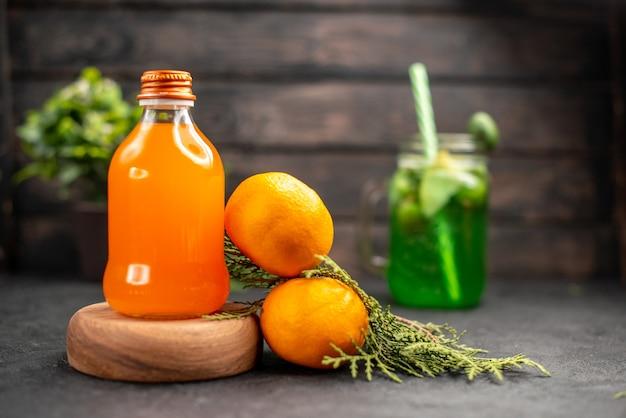 Vista frontal de jugo de naranja fresco en botella sobre tablero de madera