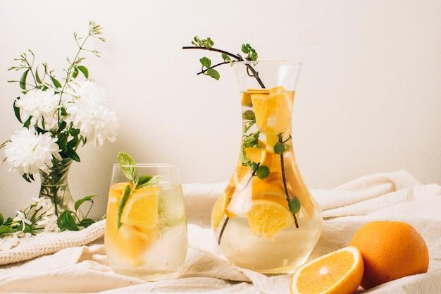 Vista frontal de jugo de naranja en jarra y vaso.