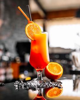 Vista frontal de jugo de naranja con una rodaja de naranja