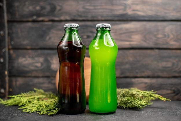 Vista frontal de jugos negros y verdes en botellas, tablero de madera, ramas de pino