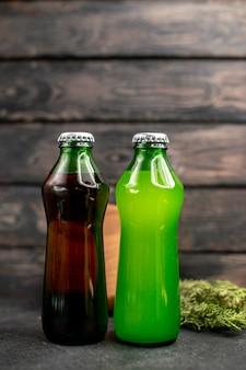Vista frontal jugos negros y verdes en botellas tablero de madera sobre mesa de madera