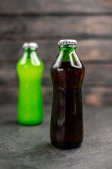 Vista frontal de jugos negros y verdes en botellas.