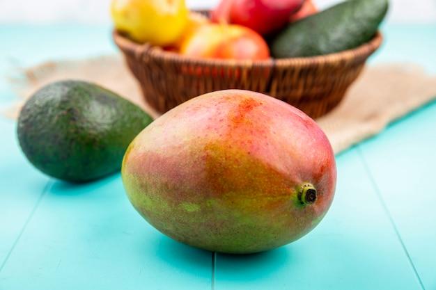 Vista frontal de jugoso mango con un cubo de frutas frescas sobre tela de saco sobre superficie azul