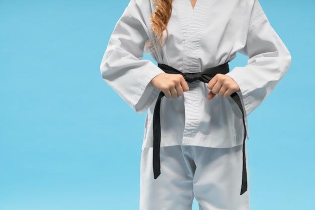Vista frontal del kimono en pequeño luchador manteniendo el cinturón negro