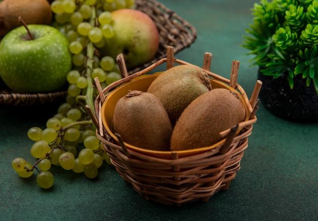 Vista frontal de kiwi en una canasta con uvas verdes y manzanas sobre un fondo verde