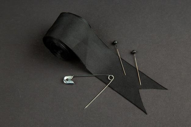 Vista frontal lazo negro con alfiler en la superficie oscura oscuridad ropa foto coser tejer color