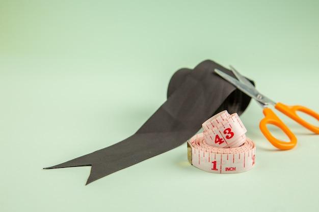 Vista frontal lazo negro con tijeras sobre superficie verde ropa foto coser agujas coser alfileres de colores