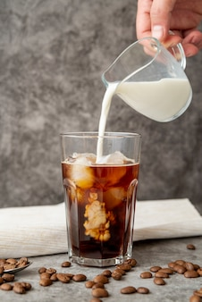 Vista frontal leche vertida en café helado