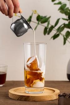 Vista frontal de leche vertiendo sobre café helado