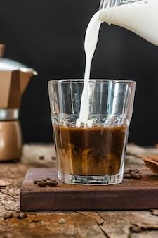 Vista frontal de la leche se vierte en un vaso con café