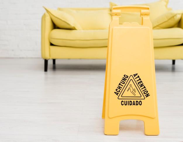 Vista frontal del letrero de piso mojado con sofá