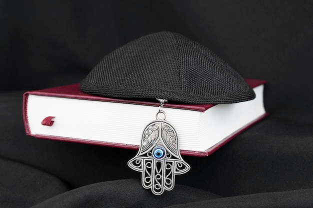 Vista frontal del libro sagrado con kipá y hamsa