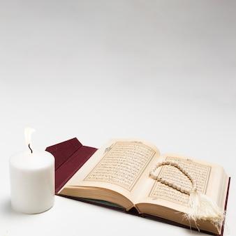 Vista frontal libro sagrado con vela encendida