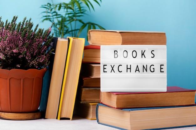 Vista frontal de libros apilados con caja de luz y maceta de plantas