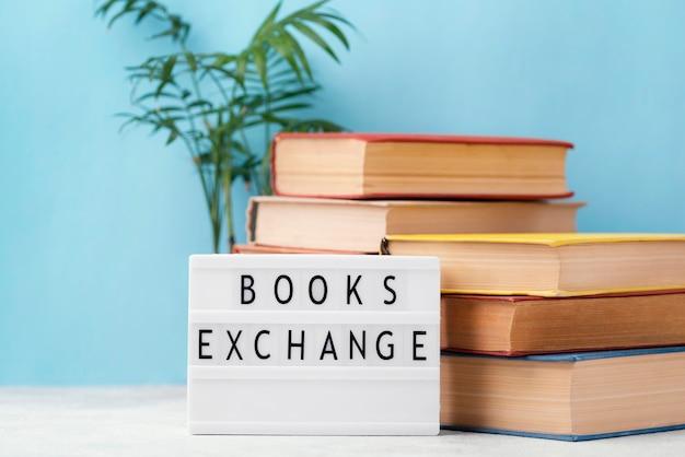 Vista frontal de libros apilados con caja de luz y planta