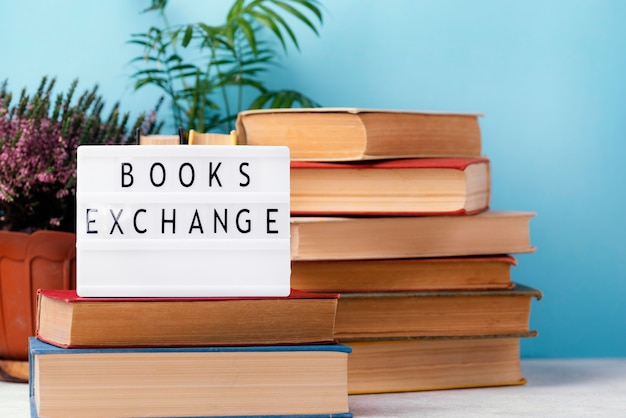 Vista frontal de libros apilados con maceta de plantas y caja de luz