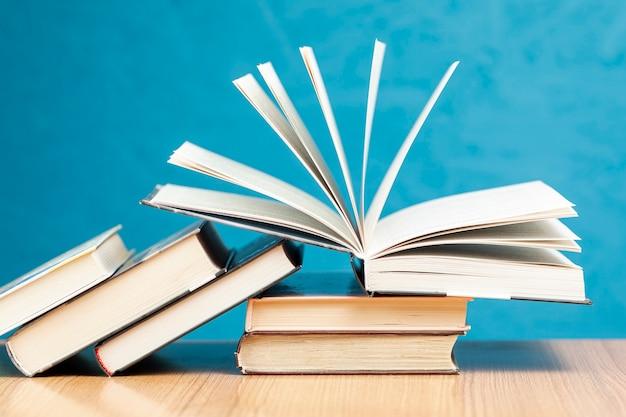 Vista frontal de libros sobre la mesa con fondo azul.