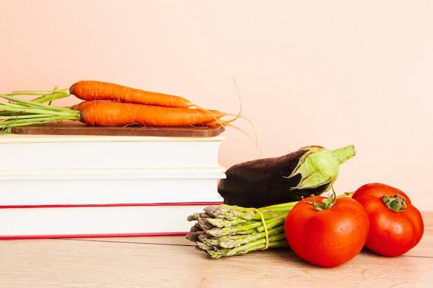 Vista frontal de libros y verduras con fondo liso