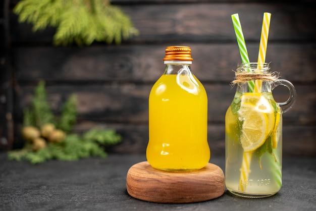 Vista frontal de limonada fresca y jugo de naranja en botellas