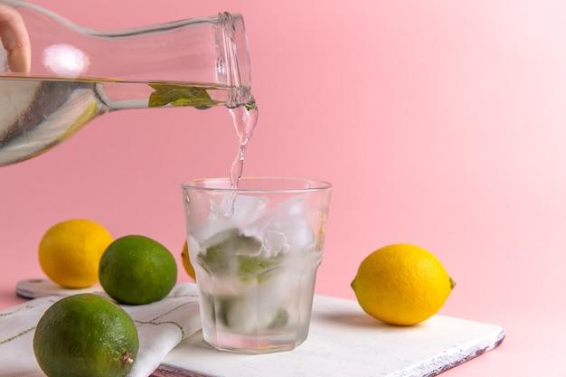 Vista frontal de limonada fría fresca con hielo dentro del vaso junto con limones frescos en la pared rosa