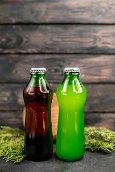 Vista frontal de limonada verde negro en botellas de tablero de madera