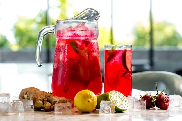 Vista frontal limonada vigorizante con fresas de lima limón y jengibre