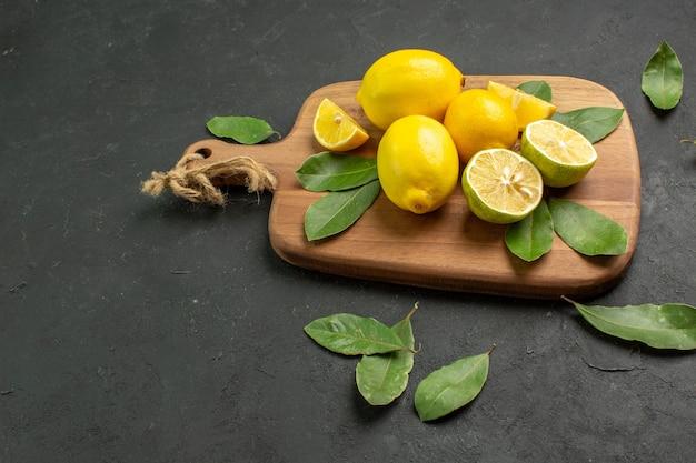Vista frontal limones amarillos frescos frutos amargos sobre fondo oscuro