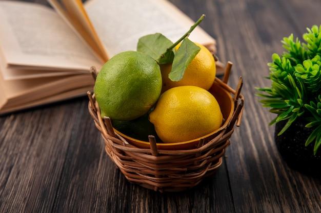 Vista frontal de limones con limas en canasta con libro abierto sobre fondo de madera