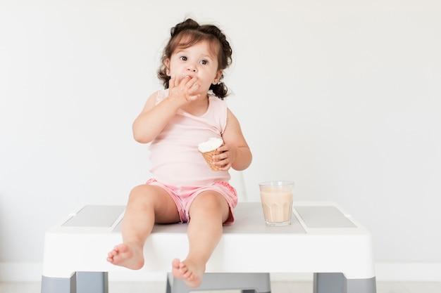 Vista frontal linda chica comiendo helado