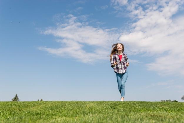 Vista frontal linda chica corriendo sobre la hierba