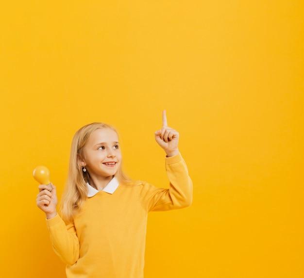 Vista frontal de linda chica posando mientras sostiene la bombilla de luz amarilla y apuntando hacia arriba