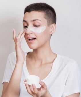 Vista frontal linda mujer con cabello corto con una crema para la piel