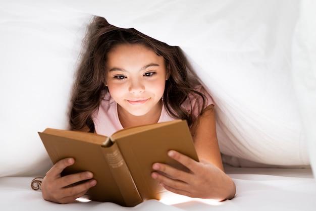 Vista frontal linda niña leyendo