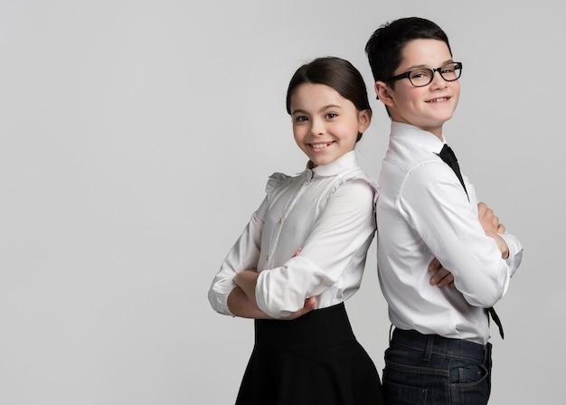 Vista frontal linda niña y niño posando juntos