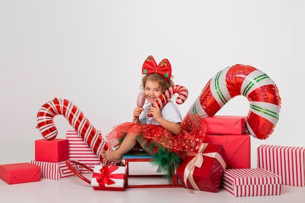 Vista frontal linda niña rodeada de elementos navideños