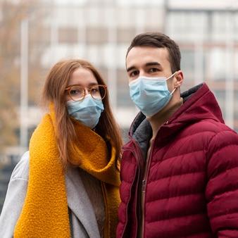 Vista frontal de la linda pareja con máscaras médicas
