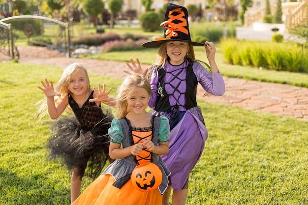 Vista frontal de lindas niñas con disfraces de halloween