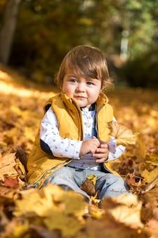 Vista frontal lindo bebé en hojas coloridas