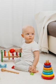 Vista frontal del lindo bebé con juguetes en casa