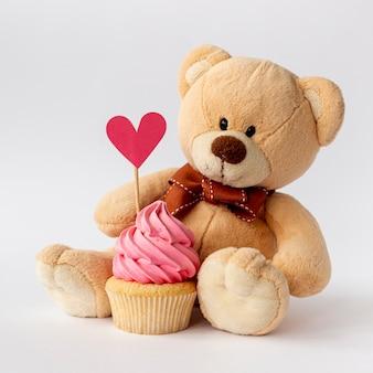 Vista frontal de lindo bebé niño cupcake y osito de peluche