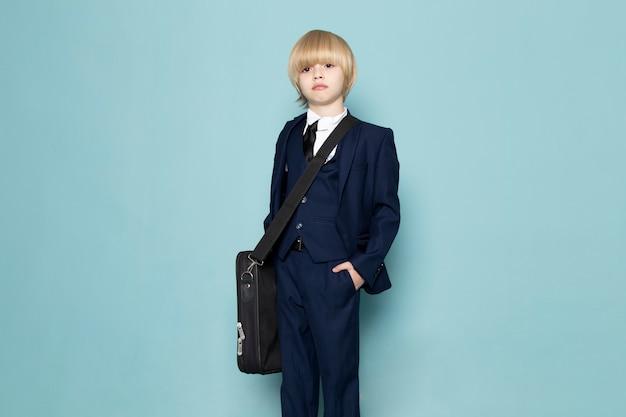 Una vista frontal lindo chico de negocios en traje clásico azul con bolso negro posando moda de trabajo de negocios
