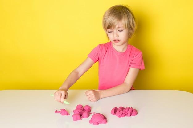 Una vista frontal lindo niño adorable en camiseta rosa jugando con arena cinética colorida
