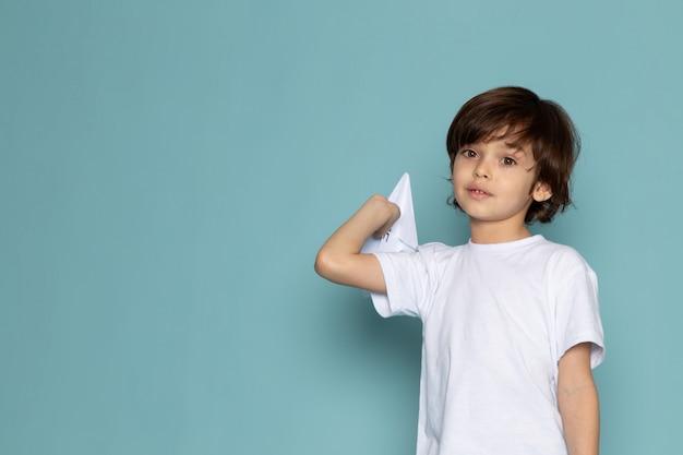 Vista frontal lindo niño adorable dulce sosteniendo avión de papel en el escritorio azul