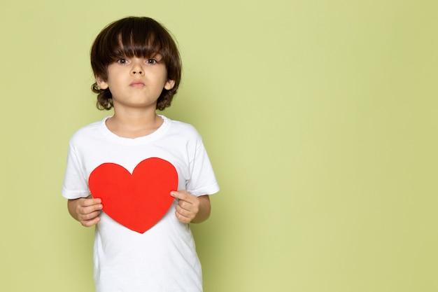 Una vista frontal lindo niño en camiseta blanca con forma de corazón en el espacio de color piedra