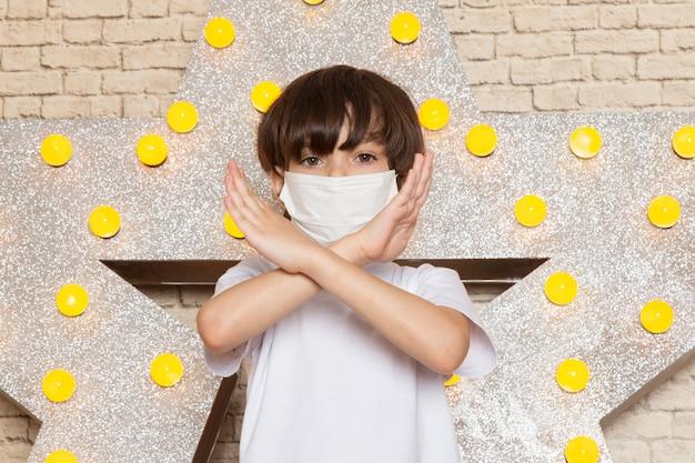 Una vista frontal lindo niño pequeño en camiseta blanca jeans oscuros máscara blanca estéril en la estrella diseñada soporte amarillo y fondo claro