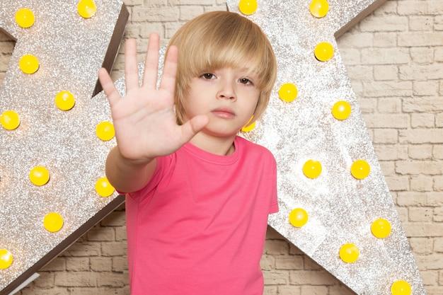Una vista frontal lindo niño pequeño en camiseta rosa jeans grises en la estrella diseñada soporte amarillo y fondo claro