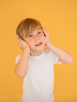 Vista frontal del lindo niño pequeño escuchando música