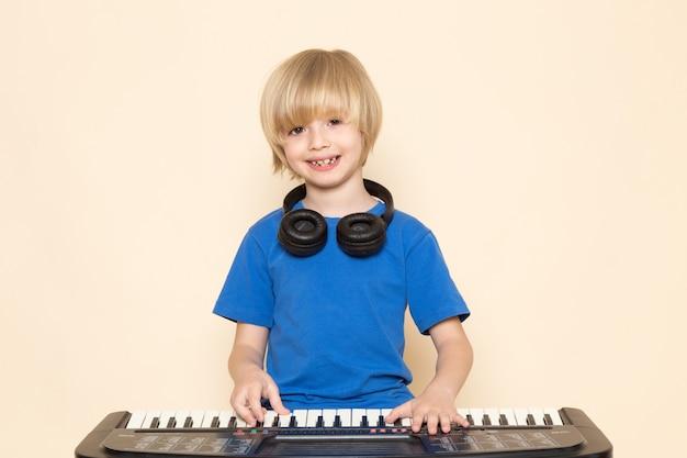 Una vista frontal lindo niño pequeño sonriendo en camiseta azul con auriculares negros tocando un pequeño y lindo piano